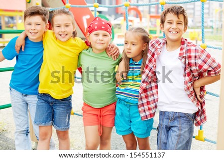 Happy friends looking at camera on playground outdoors  - stock photo
