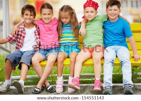 Happy friends looking at camera while sitting on bench outdoors  - stock photo