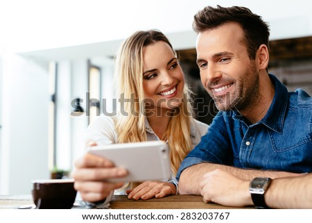Happy friends looking at smartphone at cafe - stock photo