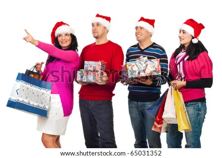 Happy friends people at shopping for Christmas,one of woman pointing up and showing something to her friends isolated on white background - stock photo