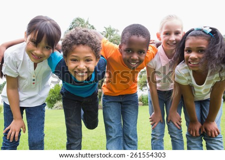 Happy friends playing in the park on a sunny day - stock photo