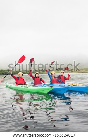 Happy friends rowing on a lake and cheering at camera - stock photo