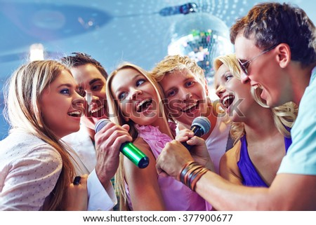 Happy friends singing karaoke at party - stock photo