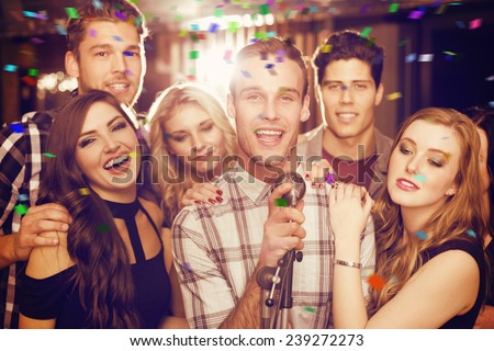 Happy friends singing karaoke together against flying colours - stock photo