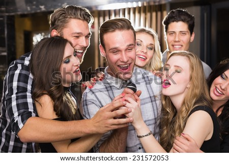 Happy friends singing karaoke together in a bar - stock photo