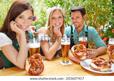 Happy friends sitting in beer garden in Bavaria with pretzel - stock photo
