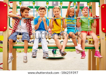 Happy friends sitting on swing and looking at camera - stock photo