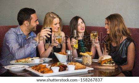Happy friends sitting together having dinner in a restaurant - stock photo