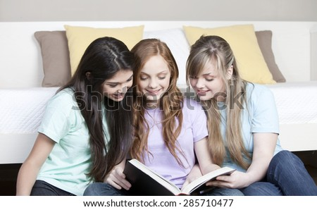 Happy friends studying with book - stock photo