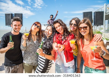 Happy friends taking a self portrait with selfie stick at a open air party - People dancing and partying while the disc jockey mixes two song tracks at a summer concert - stock photo
