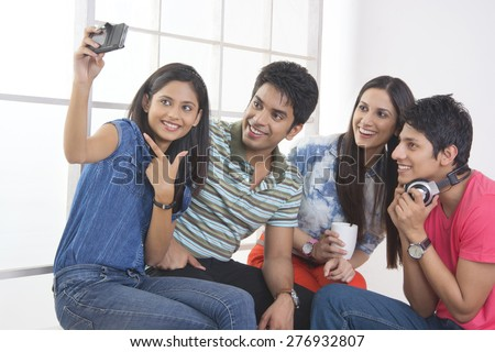 Happy friends taking self portrait through smart phone in college - stock photo