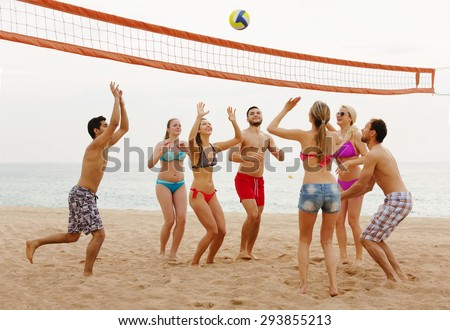 Happy friends throwing ball over net and laughing  - stock photo