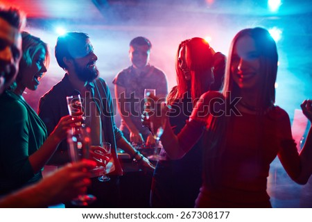 Happy friends toasting at night party - stock photo