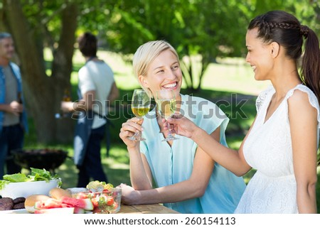 Happy friends toasting at the park on a sunny day - stock photo