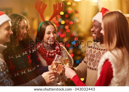 Happy friends toasting with bubbly champagne on Christmas eve - stock photo