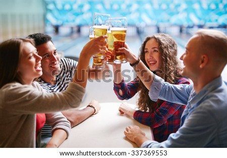Happy friends toasting with glasses of beer - stock photo