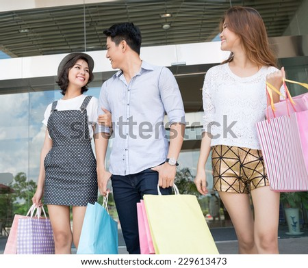 Happy friends walking with paper bags outdoors - stock photo