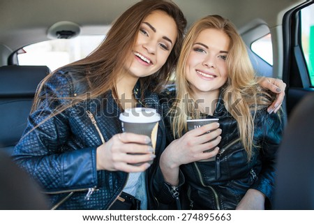 Happy friends with cup of coffee in car. Holiday trip of friends - stock photo