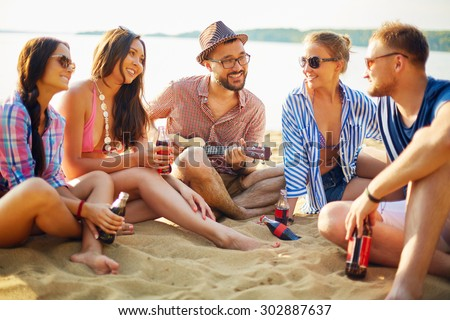 Happy friends with drinks sitting on sand by water - stock photo