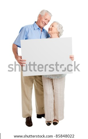 Happy full length senior couple standing together and holding a white board isolated on white background - stock photo