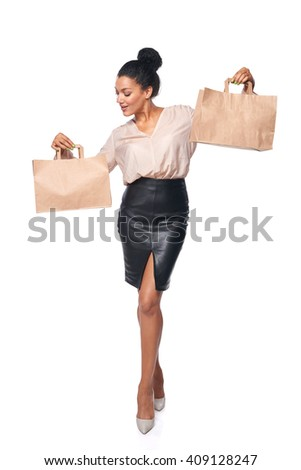 Happy full length woman holding a blank copy space paper shopping bag in every hand, over white background - stock photo