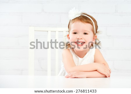 Happy fun funny girl child laughing at the empty white table - stock photo