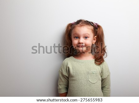 Happy fun girl looking with smile on blue wall background - stock photo