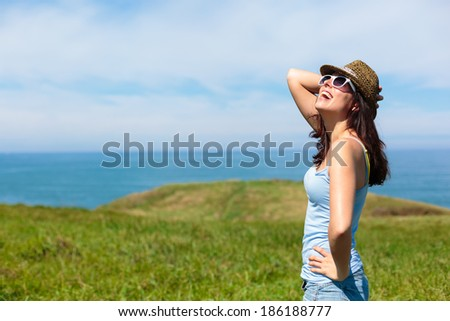 Happy funky woman enjoying nature travel in Asturias coast, Spain. Female on summer or spring leisure vacation towards the sea. - stock photo