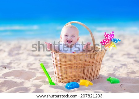 Happy funny baby, adorable blond laughing boy sitting in a basket playing with plastic beach toys, colorful bucket and shovel having fun during family picnic on tropical ocean coast - stock photo