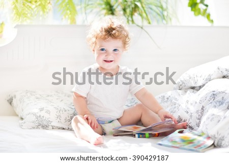 Happy funny baby reading a book in her parents bed on a sunny morning - stock photo