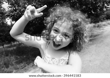 Happy, funny, crazy little girl having fun outdoors in the summer. Adorable, cute curly child, kid fooling, making funny faces, grimaces on beautiful summer day. Black and white photo. - stock photo