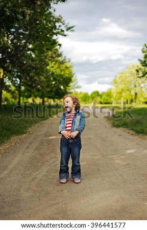 Happy, funny, little girl having fun outdoors. Adorable, cute curly child, kid fooling, making funny faces, grimaces and showing tongue on the road beautiful summer day. - stock photo