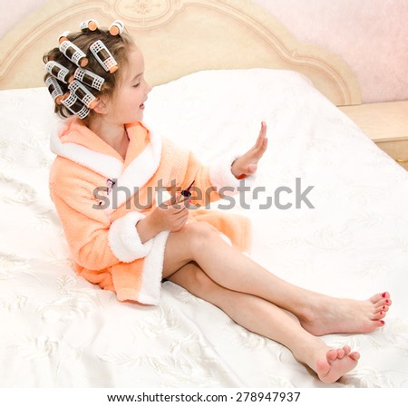 Happy funny little girl polishing her nails with curlers in bathrobe on the bed - stock photo