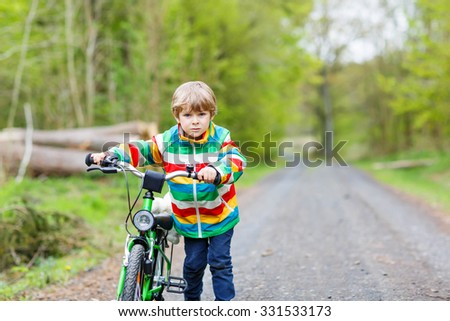 Happy funny little kid boy in colorful raincoat pushing his bicycle on cold day in forest. Active leisure for children outdoors. Happy carefree childhood concept. - stock photo