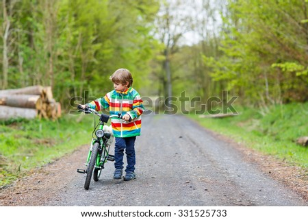 Happy funny little kid boy in colorful raincoat riding his first bike on cold day in forest. Active leisure for children outdoors. Happy carefree childhood concept. - stock photo