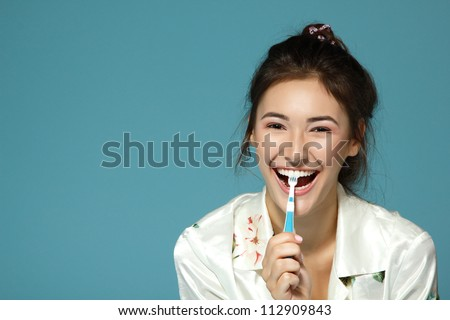 Happy funny teen girl brush her teeth. Morning theme. Over blue background. - stock photo