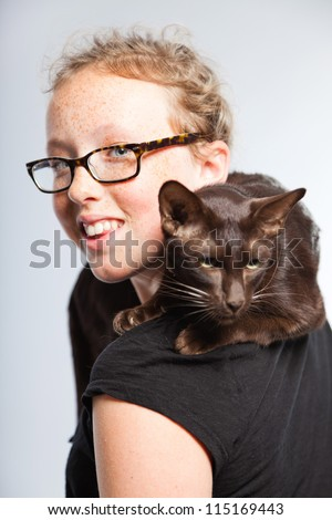 Happy funny teenage girl holding brown oriental cat. Curly blonde hair. Wearing glasses. Expressive face. Studio shot isolated on grey background. - stock photo