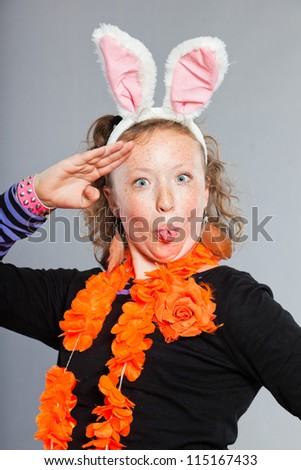 Happy funny teenage girl with curly blonde hair. Wearing bunny ears and party decoration. Expressive face. Studio shot isolated on grey background. - stock photo