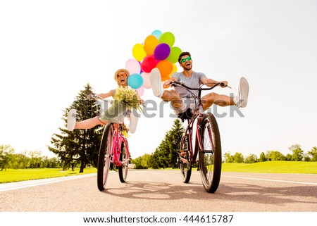 Happy funny young couple riding on bicycle with raised legs - stock photo
