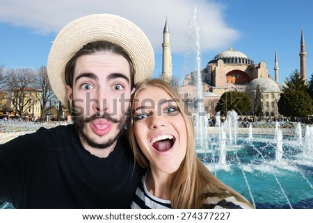 Happy, funny, young couple taking a self portrait photo, selfie, in front of the Aya Sofia mosque in Istanbul, Turkey - stock photo