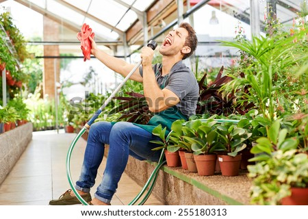 Happy gardener singing in water hose in a greenhouse of a nursery shop - stock photo