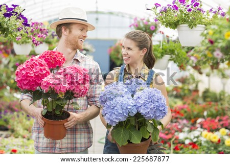 Happy gardeners looking at each other while holding flower pots at greenhouse - stock photo