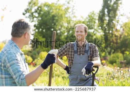Happy gardeners talking at plant nursery - stock photo