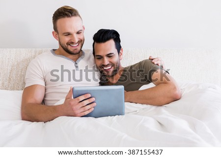 Happy gay couple using tablet in bed - stock photo