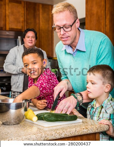 Happy gay fathers with their children in the kitchen - stock photo