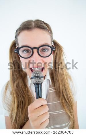 Happy geeky hipster singing with microphone on white background - stock photo