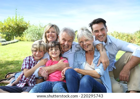 Happy 3 generation family in grandparents' backyard - stock photo