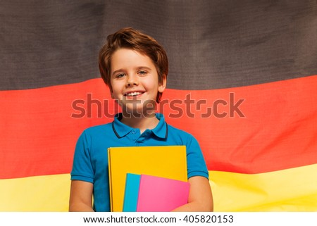 Happy German schoolboy with textbooks in his hand - stock photo