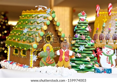 Happy gingerbread family and snowman gathered by the house and christmas tree as Christmas fun decoration - stock photo