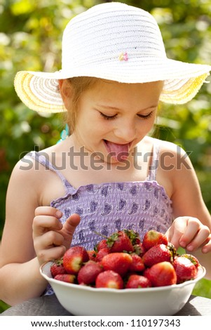 Happy girl a plate full of ripe strawberries - stock photo